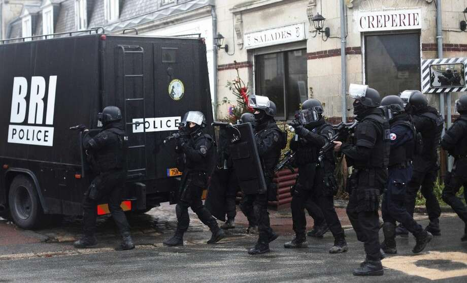 French riot officers on patrol Thursday in Longpont. Scattered gunfire and explosions shook France as its frightened yet defiant citizens held a day of mourning for 12 people slain at a Paris newspaper. Photo: Thibault Camus