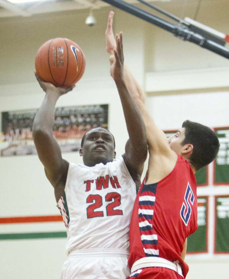 The Woodlands guard Romeo Wilbert goes up for a shot as Atascocita guard Paris Marquez defends during a high school boys basketball game Tuesday. To view or purchase this photo and others like it, visit HCNpics.com. Photo: Jason Fochtman