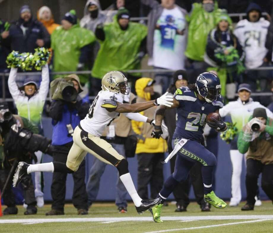 Seattle Seahawks running back Marshawn Lynch shakes off New Orleans Saints cornerback Keenan Lewis during a 31-yard touchdown run in the fourth quarter of an NFC divisional playoff game on Saturday in Seattle. Photo: Ted S. Warren