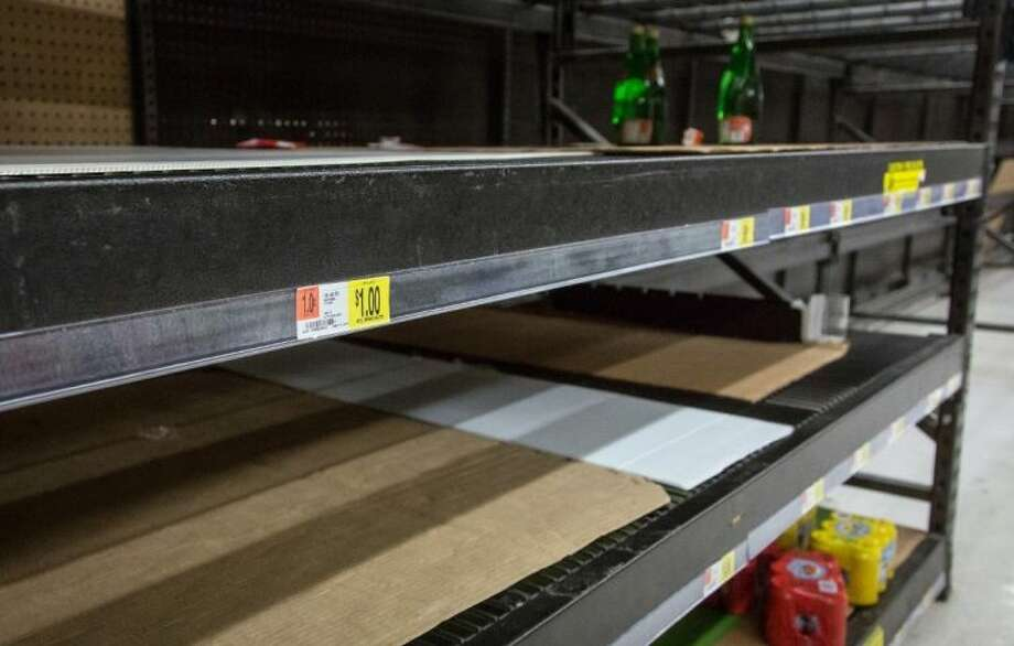 Supermarket shelves which contained bottled water stand empty as residents stock up on drinking water across Kanawha County (W.Va.) in Charleston, W.Va. on Saturday.