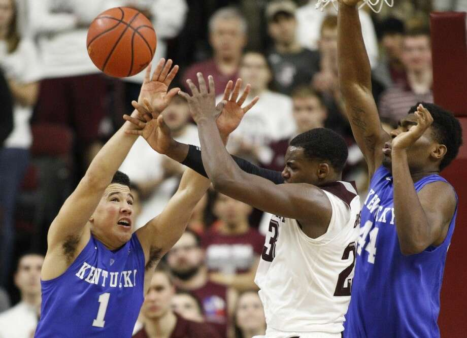 Kentucky's Devin Booker (1) and Dakari Johnson defend Texas A&M's Danuel House during overtime of an NCAA college basketball game on Saturday in College Station. Photo: Patric Schneider
