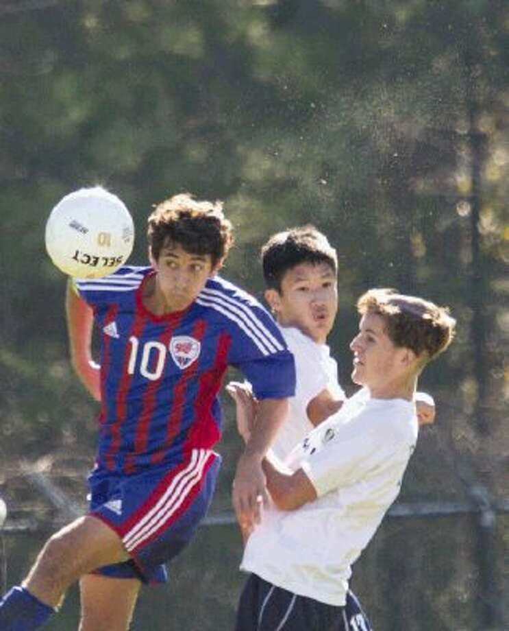 Oak Ridge's Ian Berns heads the ball after slipping between McNeil's Michael Lam, left, and Grant Geissinger during a match in the Kilt Cup on Saturday morning at The Woodlands High School. To view or purchase this photo and others like it, visit HCNpics.com. / The Conroe Courier/ The Woodland