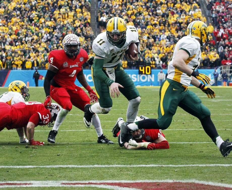 North Dakota State quarterback Carson Wentz scores the go-ahead touchdown Saturday in front of Illinois State defenders, including end David Perkins (4), during the second half of the FCS title game. Photo: TIM SHARP