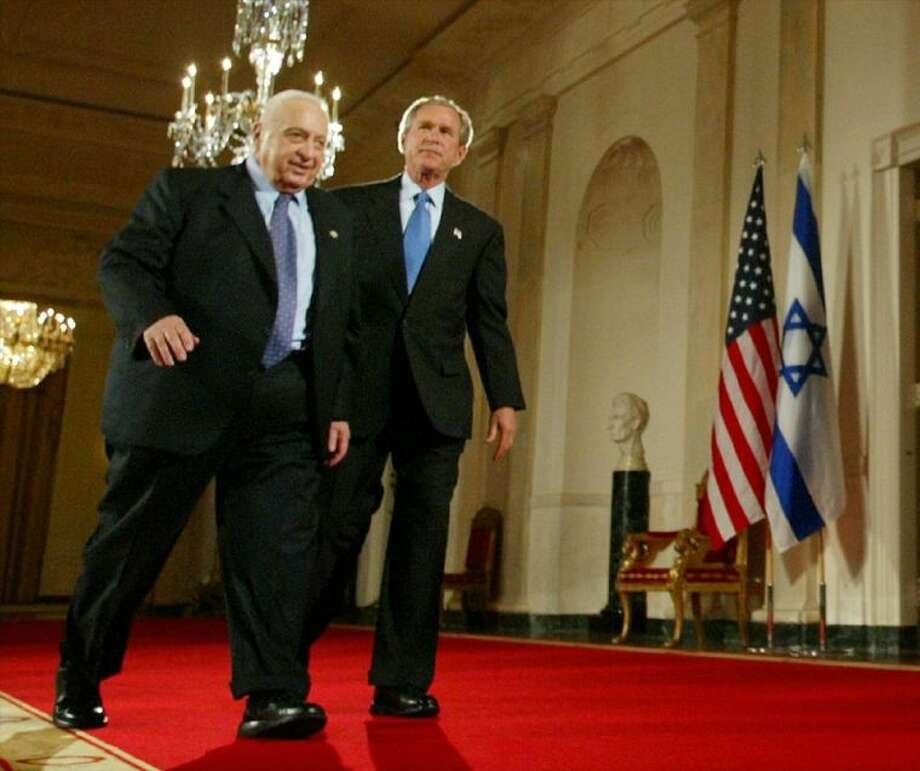 In this April 14, 2004 file photo, President George W. Bush and Israeli Prime Minister Ariel Sharon walk together at the end of a joint press conference in the Cross Hall of the White House in Washington.