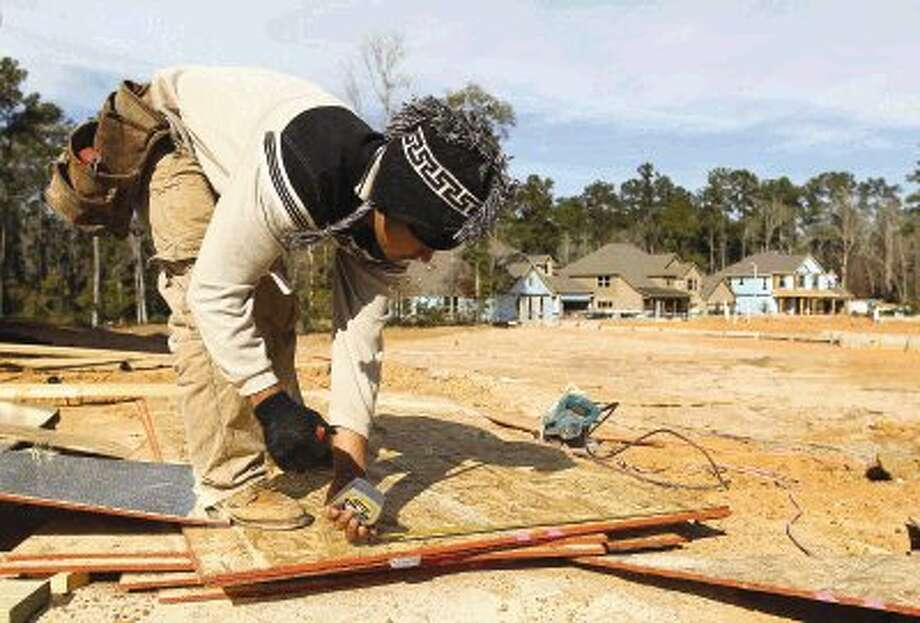 A construction worker measures out lumber for the expansion of Greystone Hills, where the developer clear cut trees for the two new phases of the subdivision. Photo: Staff Photo By Jason Fochtman / Conroe Courier