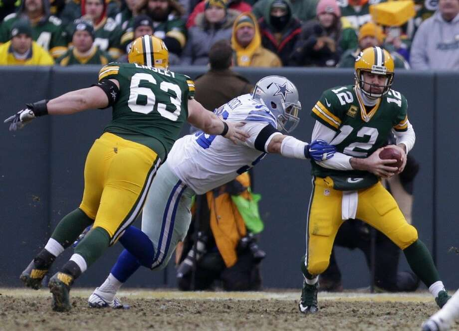Green Bay Packers quarterback Aaron Rodgers, right, escapes the pass rush of Dallas Cowboys defensive tackle Nick Hayden. The Packers won 26-21. Photo: Wm.Glasheen
