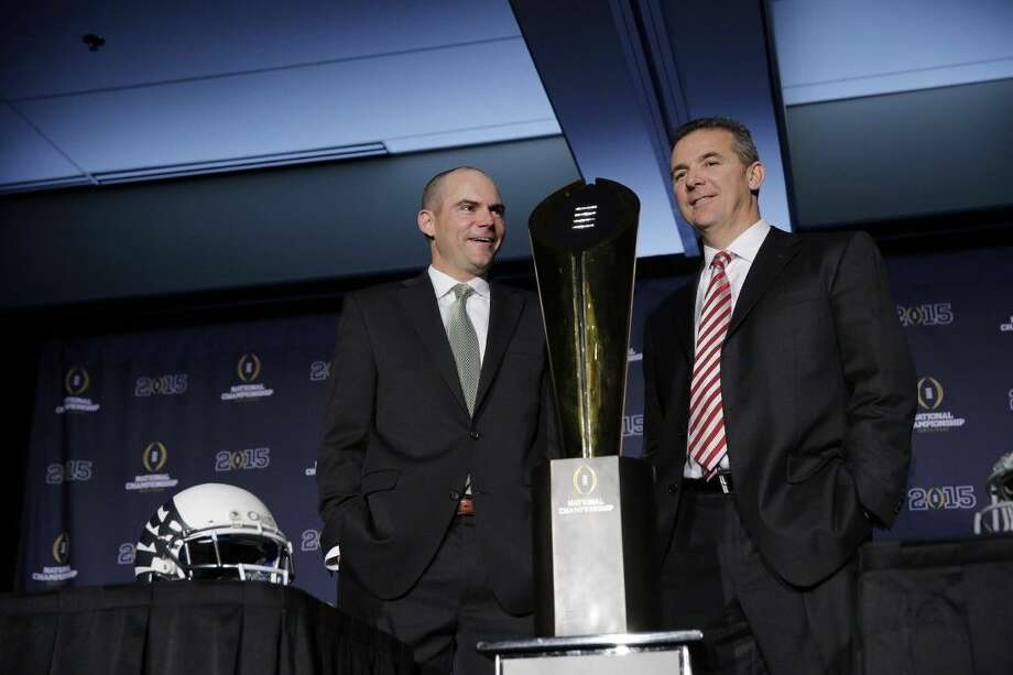 Ohio State coach Urban Meyer, right, and Oregon's Mark Helfrich pose with the championship trophy in Dallas. Oregon is a five-point favorite for tonight's game. Photo: Eric Gay