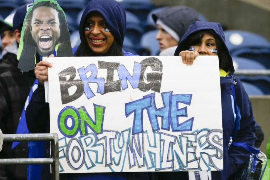 A Seattle Seahawks fan holds up a picture of cornerback Richard Sherman and a sign for the San Francisco 49ers before an NFC divisional playoff game between the Seahawks and New Orleans Saints on Saturday in Seattle. Seattle won, 23-15. Photo: Ted S. Warren