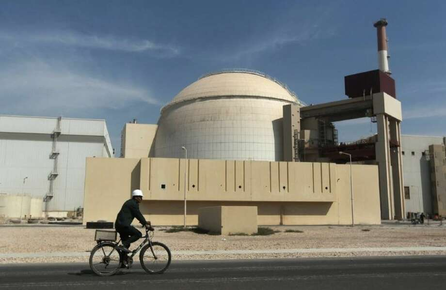 In this Oct. 26, 2010 file photo, a worker rides a bicycle in front of the reactor building of the Bushehr nuclear power plant, just outside the southern city of Bushehr. Photo: Majid Asgaripour