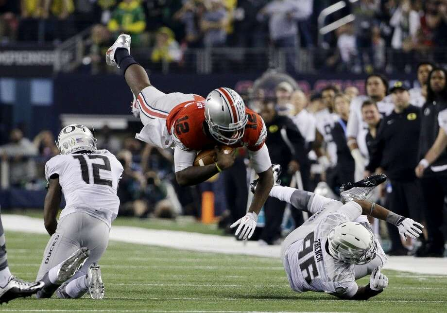 Ohio State's Cardale Jones (12) dives for a first down against Oregon. Jones and the Buckeyes defeated Oregon 35-20 to win the CFP national championship game. Photo: David J. Phillip
