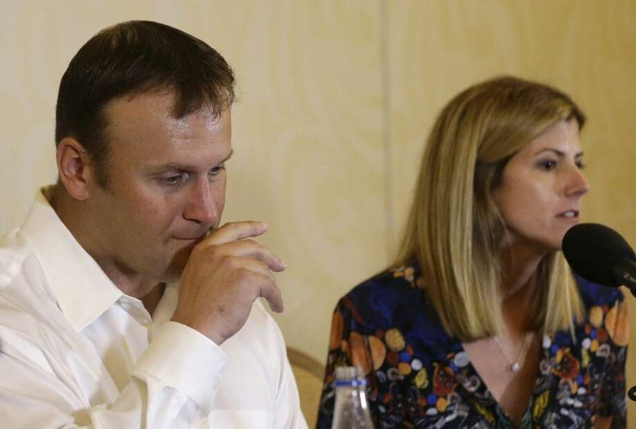 Former Miami Dolphins fullback Rob Konrad, left, listens while his wife Tammy, right, responds to a question during a news conference. Konrad fell out of his fishing boat last week and swam nine miles to shore. Photo: Lynne Sladky