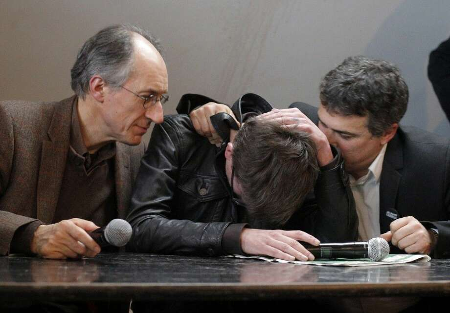 The new chief editor of French satirical magazine Charlie Hebdo, Gerard Biard, left, and columnist Patrick Pelloux, right, comfort cartoonist Renald Luzier during a press conference Tuesday in Paris. Photo: Christophe Ena