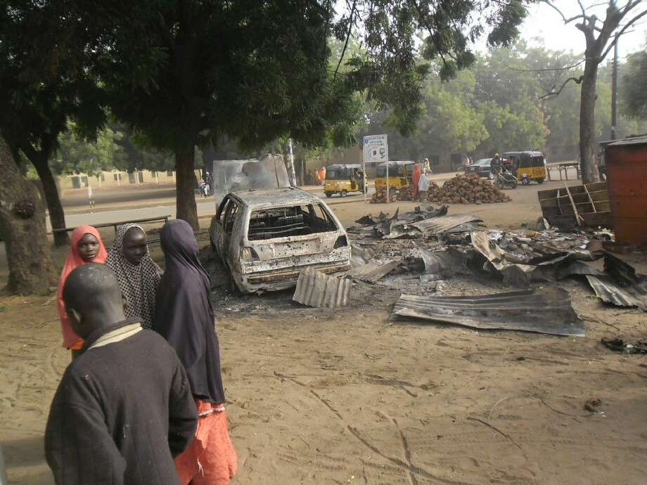 Children on Monday stand near the scene of an explosion in a mobile phone market in Potiskum, Nigeria. Two female suicide bombers targeted the busy marketplace on Sunday. Photo: Adamu Adamu