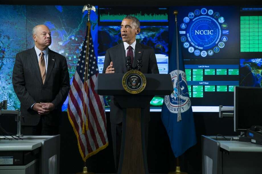 Homeland Security Secretary Jeh Johnson listens as President Barack Obama speaks Tuesday at the National Cybersecurity and Communications Integration Center in Arlington, Va. Photo: Evan Vucci