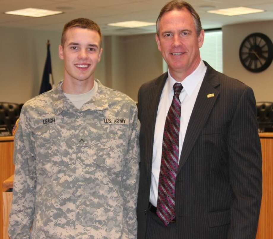 Private Cody Leach and CISD Superintendent Don Stockton pose for a picture at Monday's Montgomery County Commissioner's Court meeting. Leach was recognized as one of four CISD students who have joined the Army Reserves.