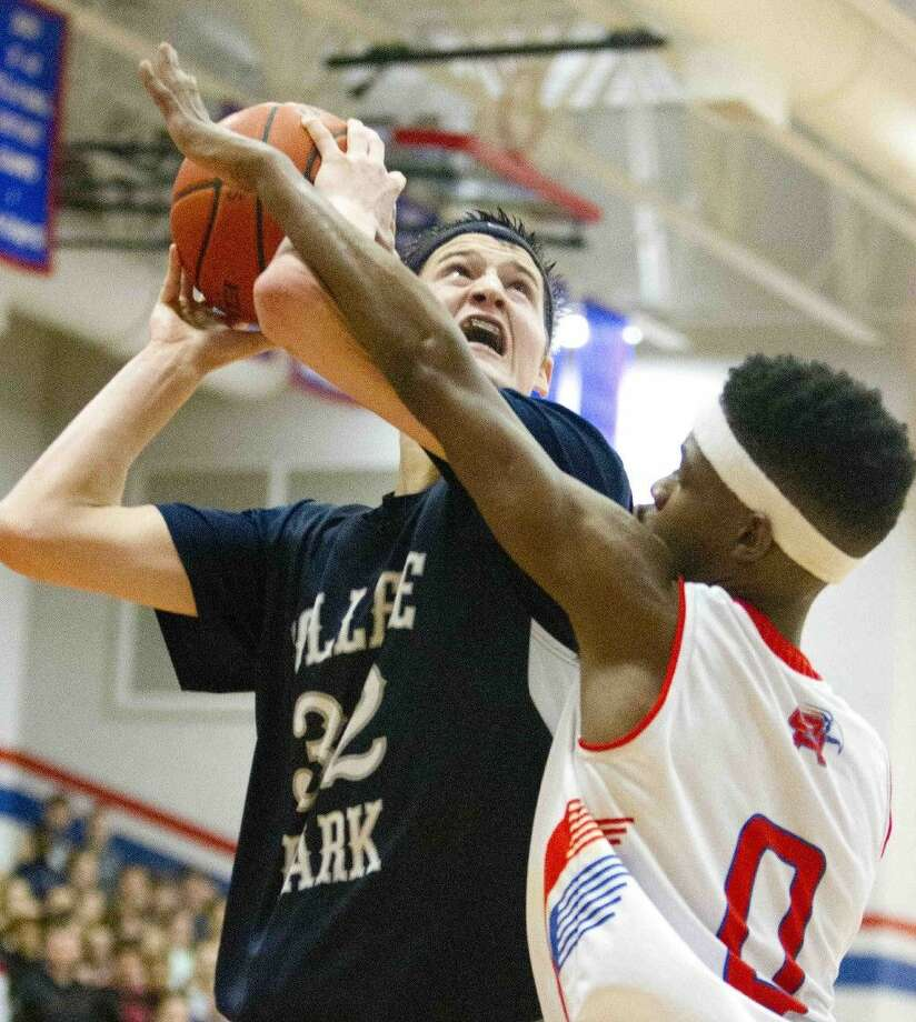 College Park's Brett Reed is fouled by Oak Ridge's Darius Love during a high school basketball game on Tuesday. Photo: Jason Fochtman