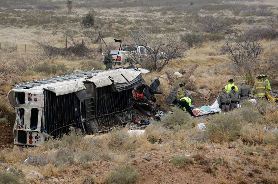 Officials investigate the scene of a prison transport bus crash in Penwell, Texas, Wednesday. Law enforcement officials said the bus carrying prisoners and corrections officers fell from an overpass in West Texas and crashed onto train tracks below, killing an unspecified number of people.