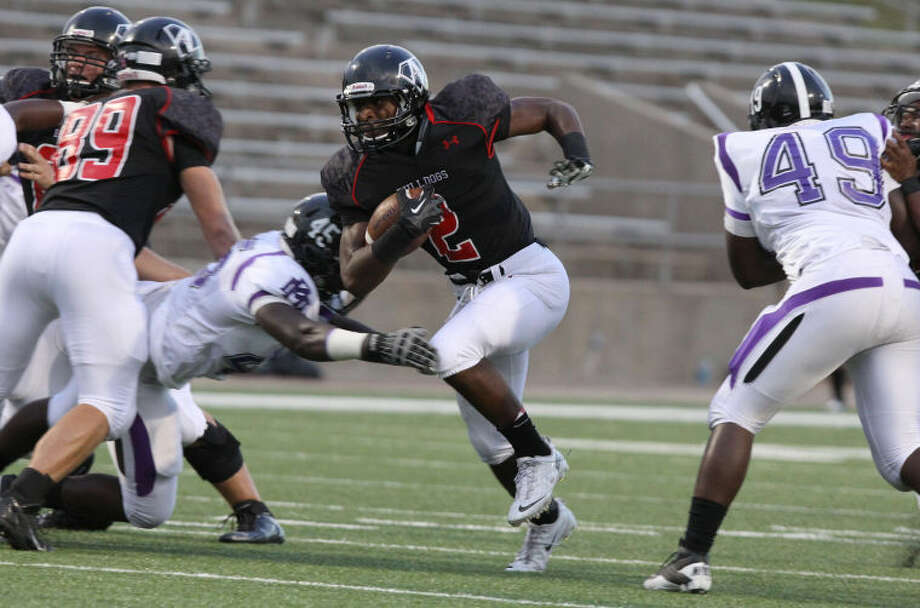 Fort Bend Austin's Bryson Olgesby runs through a hole against Morton Ranch during a non-district game Sept. 5 at Mercer Stadium in Sugar Land. Morton Ranch scored twice in the fourth quarter to win 29-24. To view or purchase photos from this game and others, visit www.HCNPics.com.