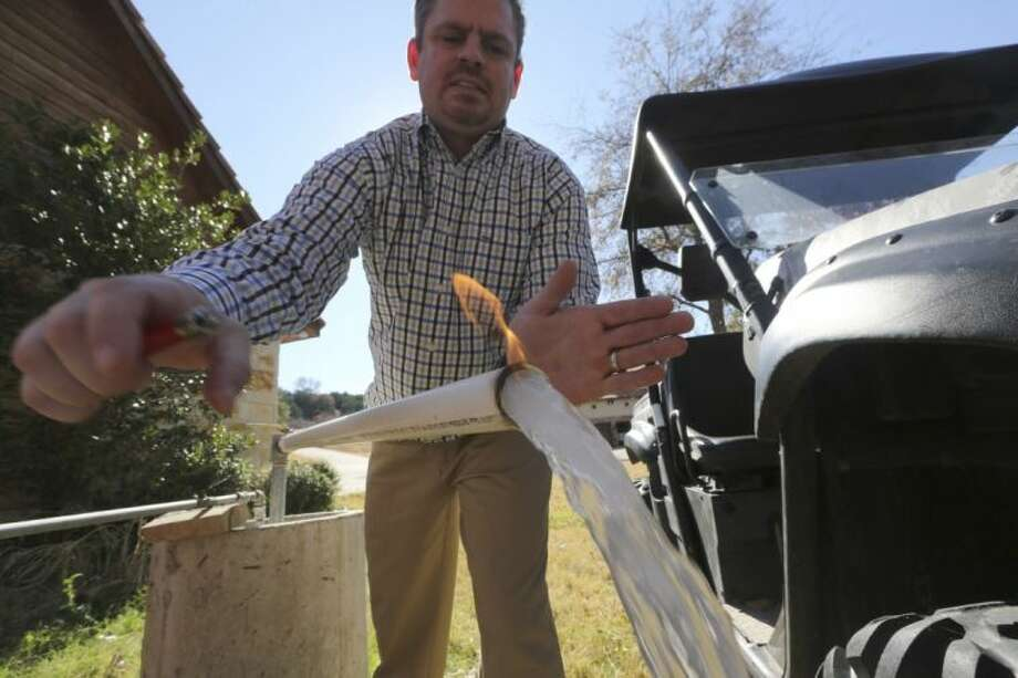 In this Nov. 26, 2012 file photo, Steve Lipsky demonstrates how his well water ignites when he puts a flame to the flowing well spigot outside his family's home in rural Parker County near Weatherford. A preliminary analysis of testing in the past year of North Texas water contaminated with explosive methane has found that the problem has spread to more residential wells, and scientists analyzing those samples believe the new evidence more conclusively points to a nearby gas drilling operation as the source of the problem.