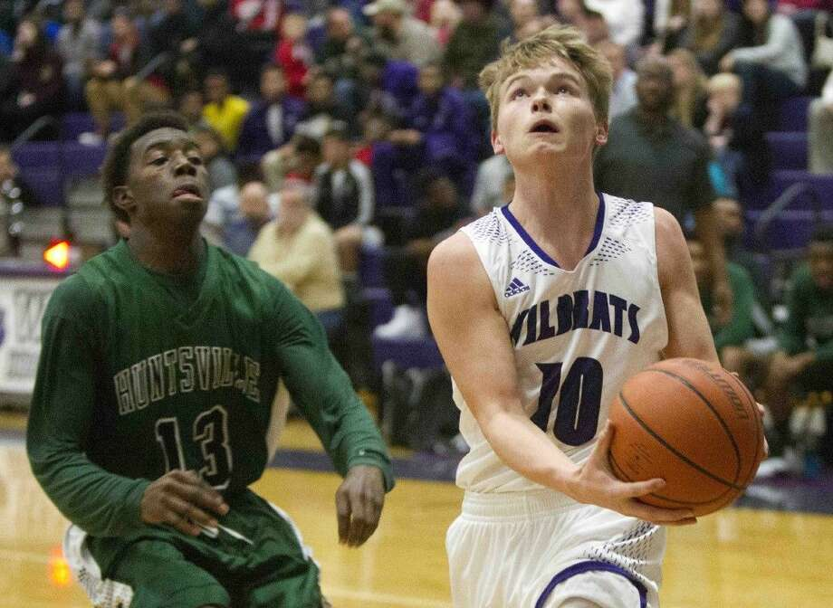 Willis' Nick Thompson goes up for a shot in the paint against Huntsville's Jayron Roberts on Friday. To view or purchase this photo and others like it, visit HCNpics.com. Photo: Jason Fochtman