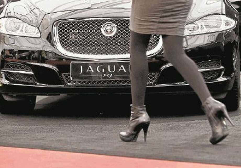In this April 3, 2013, file photo, a woman passes by a Jaguar XJ during an Auto Moto Show in Bucharest, Romania. / @WireImgId=2659156