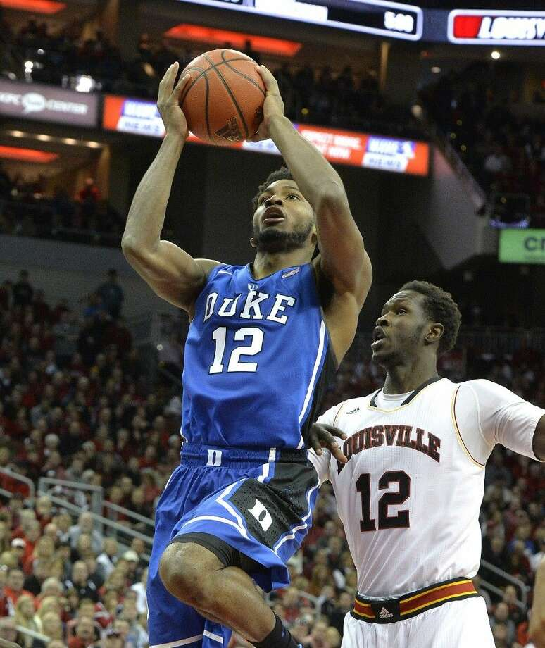 Duke's Justise Winslow, left, puts up a shot against Louisville during the first half of an NCAA college basketball game on Saturday. Photo: Timothy D. Easley