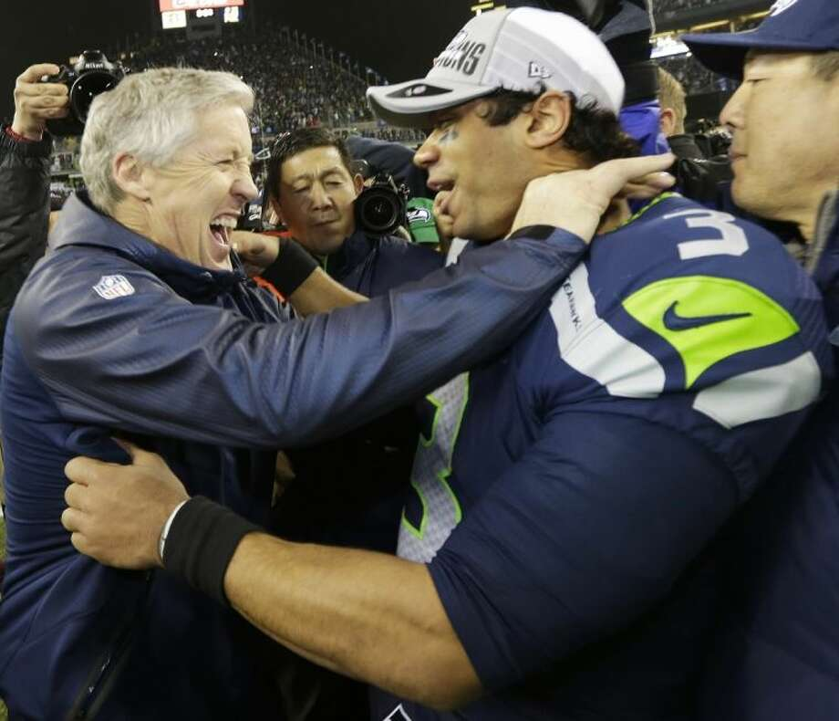 Seahawks coach Pete Carroll congratulates quarterback Russell Wilson after the Seahawks' 23-17 victory over the 49ers in the NFC title game. Photo: Ted S. Warren