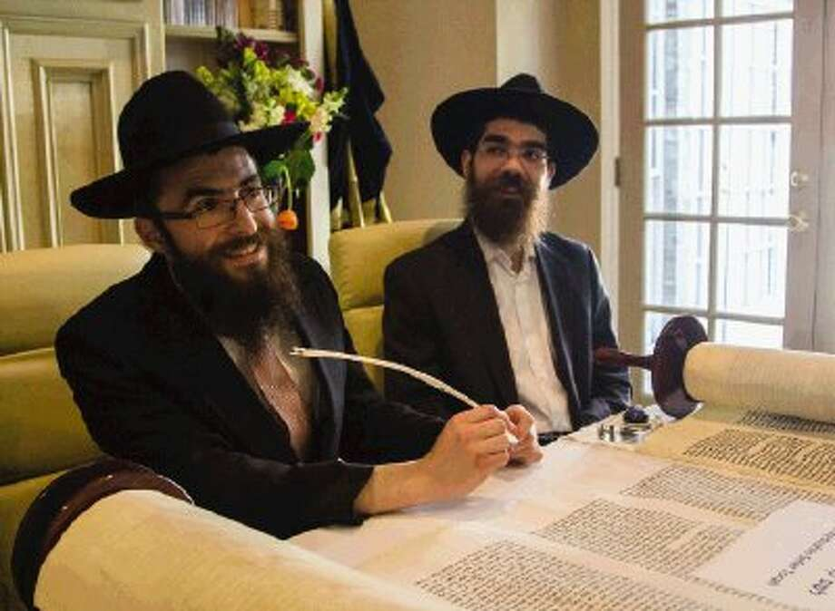 Director of Chabad of The Woodlands Rabbi Mendel Blecher sits with Chaim Pape, a sofer, and adds to a Torah scroll during a dedication of the scroll on Sunday afternoon at the home of Blecher in The Woodlands. The synagogue plans to use the Torah scroll containing the five books of Moses and 304,808 handwritten letters for ritual use. Participants later walked with the Torah scroll to Chabad of The Woodlands to continue the ceremony and enjoy music and a buffet. Go to HCNPics.com to view and purchase this photo, and others like it. Photo: Staff Photo By Ana Ramirez / The Conroe Courier/ The Woodland