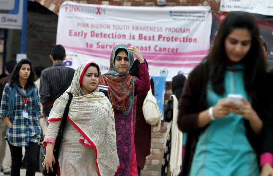 In this Wednesday, Oct. 30, 2013 photo, students walk past a banner promoting awareness on breast cancer at a university in Islamabad, Pakistan. Among Pakistani women there is very little knowledge about breast cancer. A study done at Rawalpindi General Hospital about breast cancer awareness among 600 women found nearly 70 percent totally ignorant of the disease, while 88 percent did not know about breast self-exams and 68 percent did not understand the significance of finding a lump in the breast. Photo: Anjum Naveed