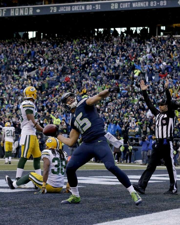 Seattle Seahawks wide receiver Jermaine Kearse throws the ball into the stands after scoring the game-winning touchdown against the Packers in overtime. Photo: Jeff Chiu