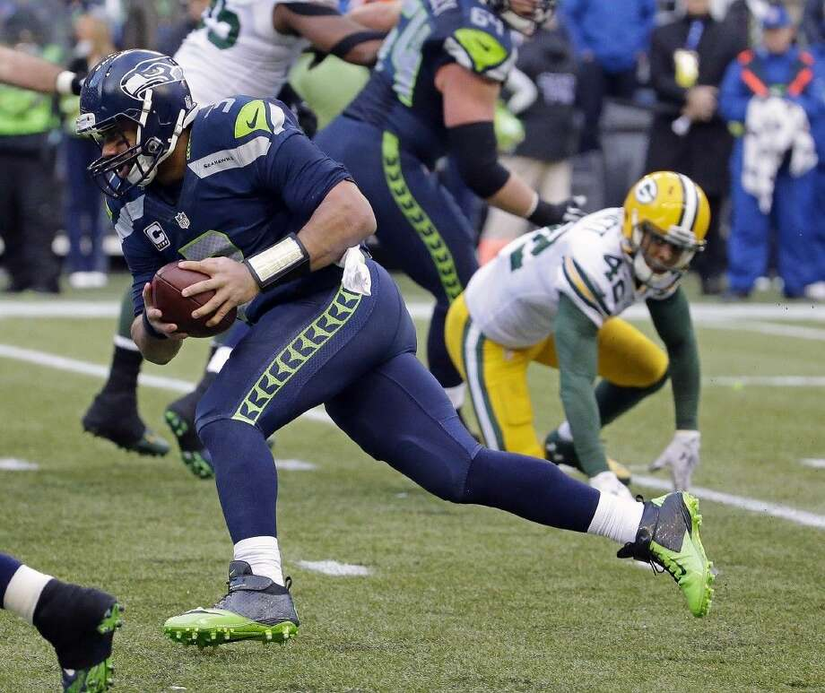 The Seahawks' Russell Wilson runs for a fourth-quarter touchdown. The Seahawks are returning to the Super Bowl after a dramatic comeback Sunday against Green Bay. Photo: Ted S. Warren