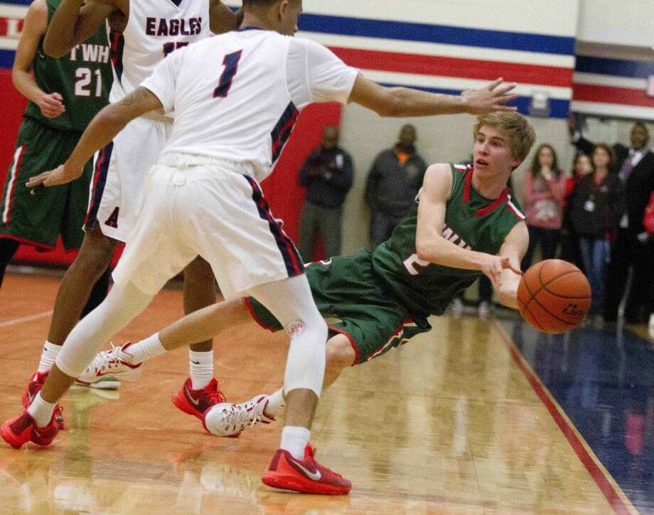 The Woodlands guard Bryce Landreville makes a pass as he falls Tuesday. Photo: Jason Fochtman