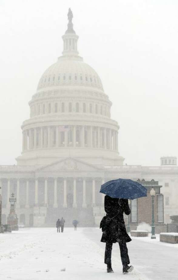 A pedestrian walks on Capitol Hill in Washington during the start of a major snowstorm, Tuesday, Jan. 21, 2014. Many government offices and schools closed before the first flake of snow, but there were signs Tuesday that significant winter weather was moving into the mid-Atlantic region as heavy snow began falling. Photo: Susan Walsh