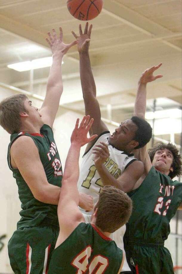The Woodlands' Cameron Burkett (12), Garrett Smith (40) and Aaron Kovach (23) triple-team Conroe guard Stedman Bell near the basket. The Highlanders won 52-46. To view or purchase this photo and others like it, visit HCNpics.com. Photo: Staff Photo By Jason Fochtman
