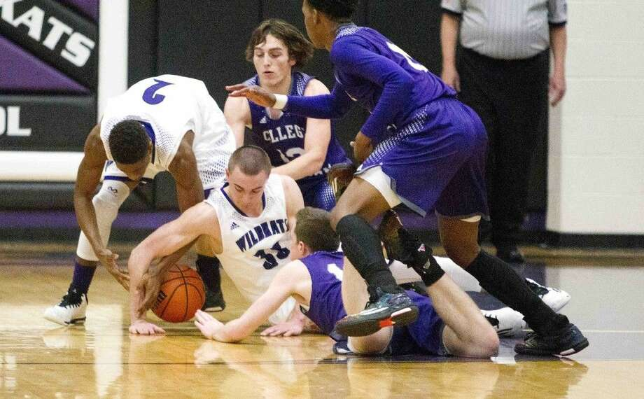 Willis' Cole Bowers and Nick McHenry try to gain possession of a loose ball during a high school basketball game on Tuesday. To view or purchase this photo and others like it, visit HCNpics.com. Photo: Jason Fochtman