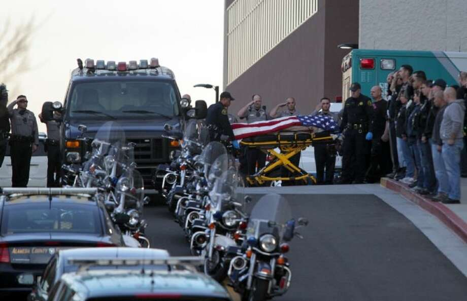 Law enforcement officers salute as the body of a Bay Area Rapid Transit police officer draped with the American flag is loaded into an Alameda County Sheriff's Coroner vehicle in Castro Valley, Calif., Tuesday. The officer was shot while serving a probation search warrant at a residence in Dublin, Calif., according to authorities. Photo: Anda Chu