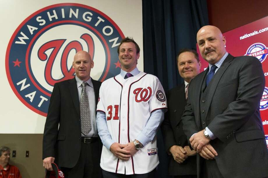 Washington Nationals pitcher Max Scherzer, second from left, poses for photographs during an introductory news conference at Nationals Park on Wednesday. Photo: Evan Vucci