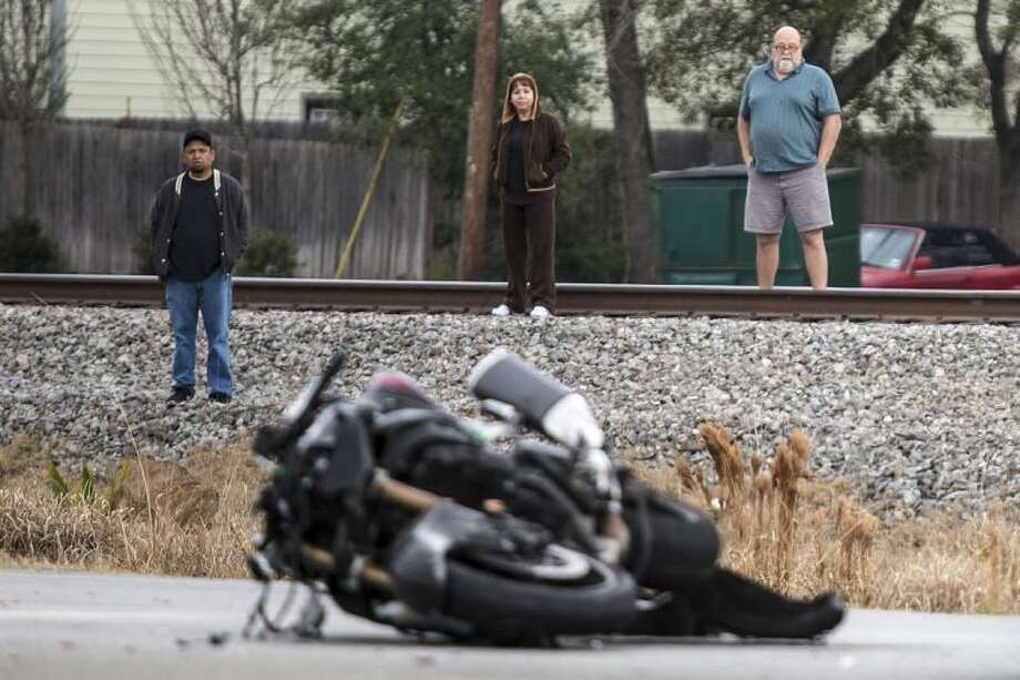 Onlookers watch as police investigate the scene of a deadly motorcycle wreck Thursday morning at the intersection of Loop 494 and East Martin Drive in Porter. The wreck occurred after a short police chase which ended in a collision with two other vehicles.