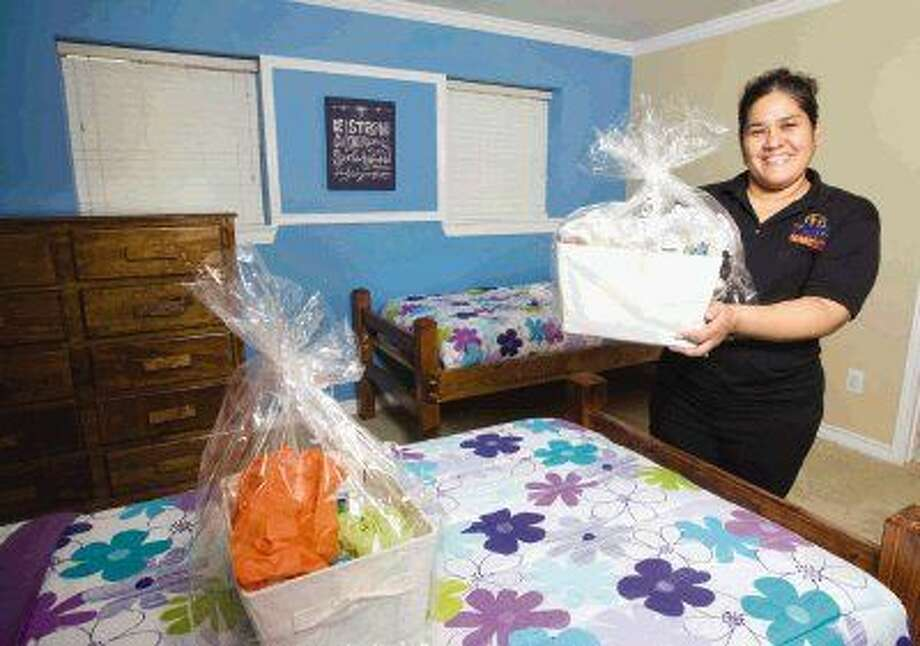 Program Director Tabitha Taylor shows off one of the care packages girls will receive at The Care Cottage in Willis. Up to 20 at-risk girls can receive services at the house at one time. Photo: Jason Fochtman