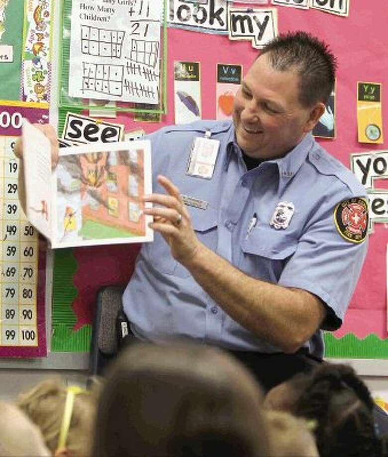 Conroe firefighter Bud Brooks reads a book about a firefighter to kindergartners during a visit to Giesinger Elementary Thursday. Firefighters from Station 5 visited the school to read to students. Photo: Staff Photo By Jason Fochtman / Conroe Courier