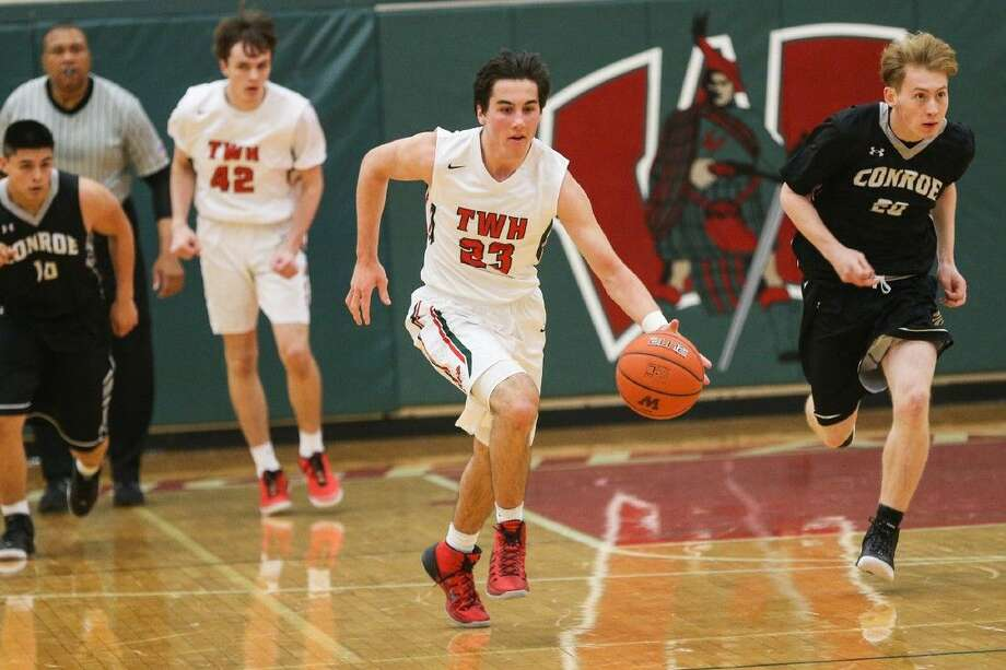The Woodlands' Jack Hammett (23) drives toward the basket against Conroe. Photo: Michael Minasi
