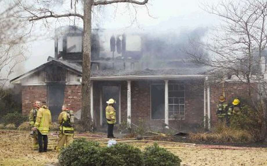 Firefighters work the scene of a house fire in Conroe Thursday. Photo: Staff Photo By Jason Fochtman / Conroe Courier