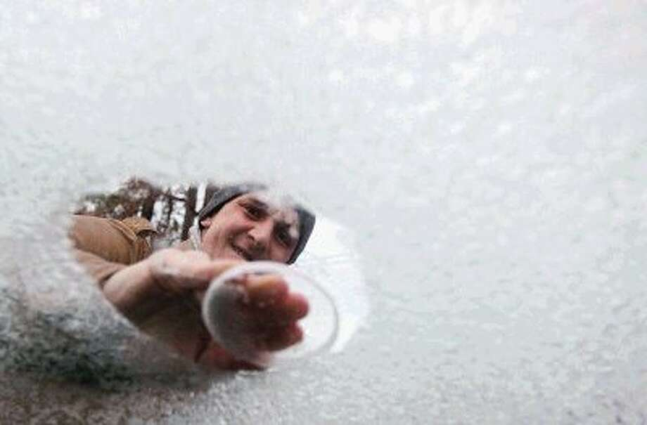 Conroe resident Michal Fiuk scrapes off the ice from his car Friday morning. Fiuk, a native of Poland, said it was minus-23 degrees in his hometown Friday morning and he was stunned many business and schools in Conroe were closed. Photo: Staff Photo By Jason Fochtman / Conroe Courier / HCN