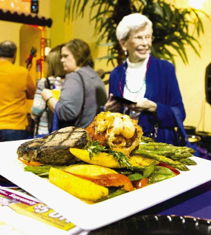A woman looks over the entrees offered at last year's Taste of the Town. About 60 restaurants and caterers will showcase their culinary skills with appetizers, entrees, pastries and desserts at the event, scheduled for Jan. 28 at The Woodlands Waterway Marriott Hotel and Convention Center.