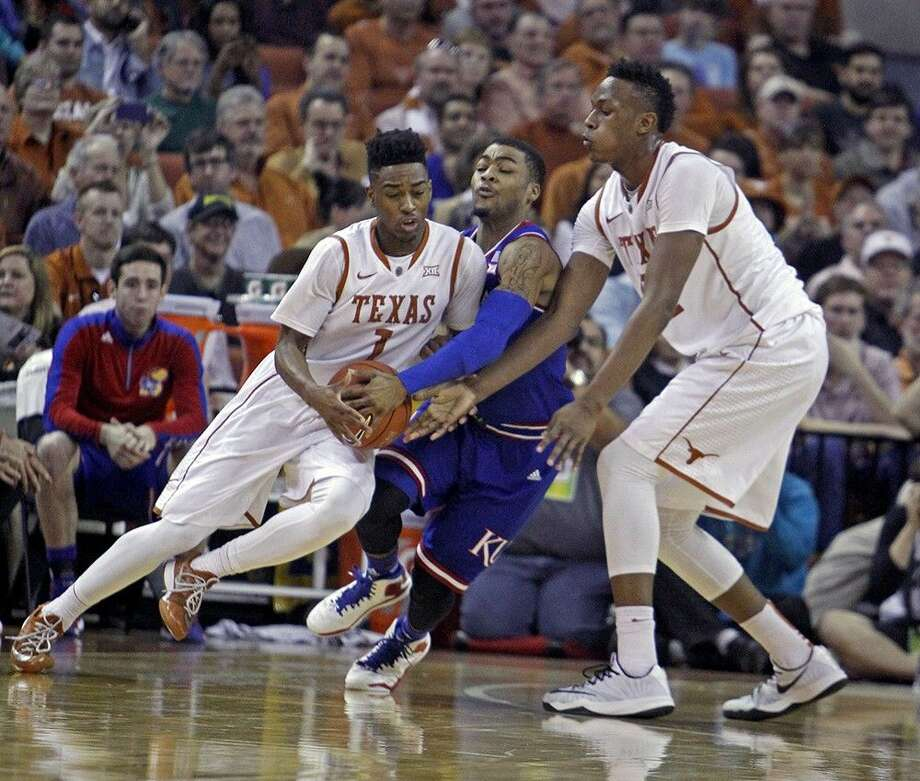 Texas guard Isaiah Taylor, left, drives around Kansas guard Frank Mason III, center, while Texas forward Myles Turner, right, sets a screen during the first half an NCAA college basketball game, Saturday in Austin. Photo: Michael Thomas