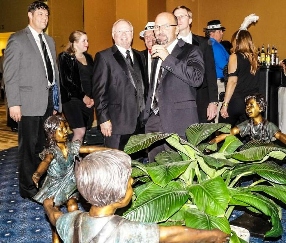 Four bronze statues of children were sponsored and donated by Spirit of Texas Bank Chairman and CEO Dean Bass (third from left) at recent fundraiser for Montgomery County Child Protective Services. The statues will be dedicated and placed on the Montgomery County Courthouse grounds in April during National Child Abuse Prevention Month.