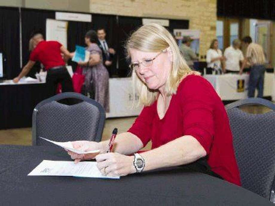 Lenais Hatfield fills out an application during the Greater Conroe/Lake Conroe Area Chamber of Commerce's annual job fair Tuesday. Photo: Jason Fochtman