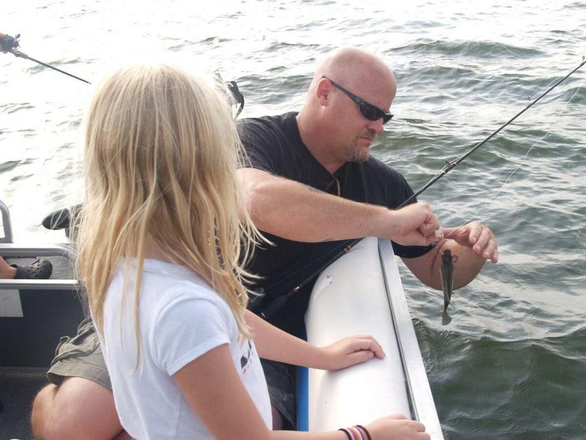A father removes a bream from the hook on his daughter's rod and reel while fishing on Lake Conroe. It doesn't get much better!