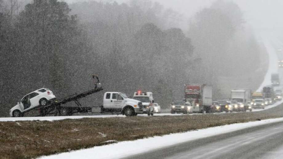 Traffic backs up as a wrecker pulls a car out of a ditch on I-65 during an unual snow Tuesday in Clanton, Ala. A rare storm left a slippery layer of ice and snow across a region unaccustomed to dealing with the wintry threat. Photo: Butch Dill