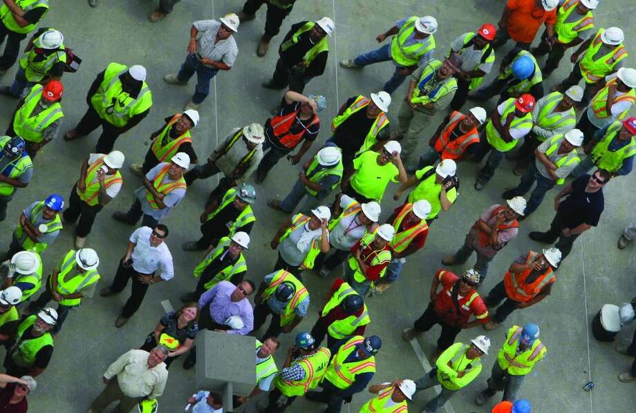 In this 2013 file photo, workers watch as a tree is hoisted to the top of Anadarko's Hackett Tower during the topping off ceremony Thursday.